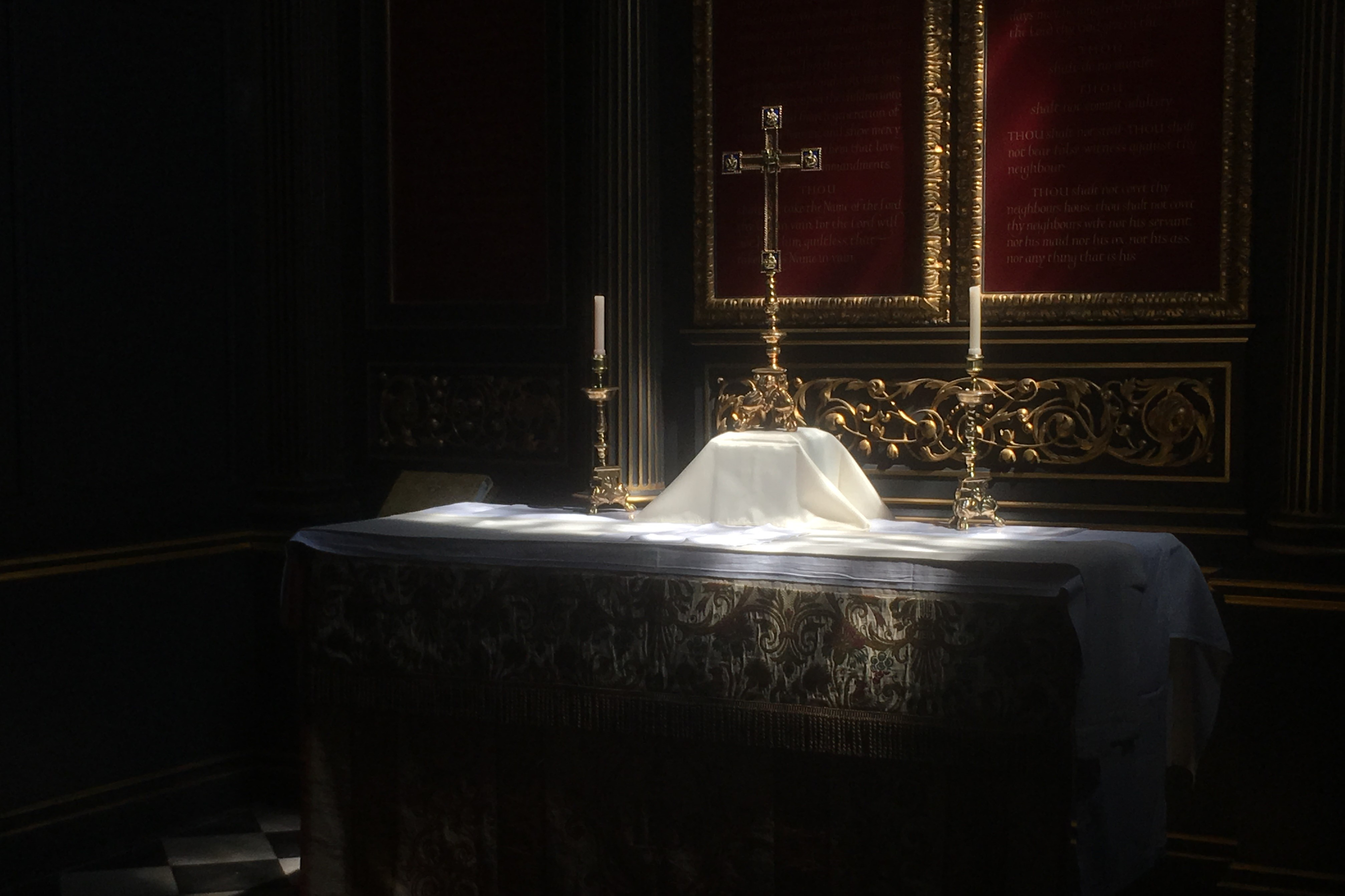 Light hitting the altar with candles and a cross