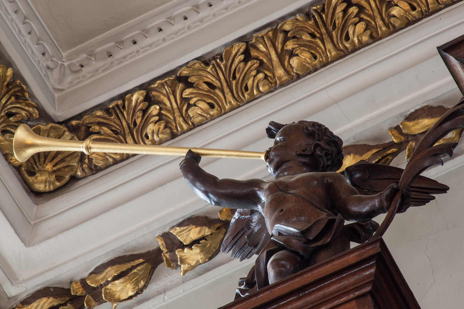 A wooden carved cherub blowing a gold trumpet on top of the organ