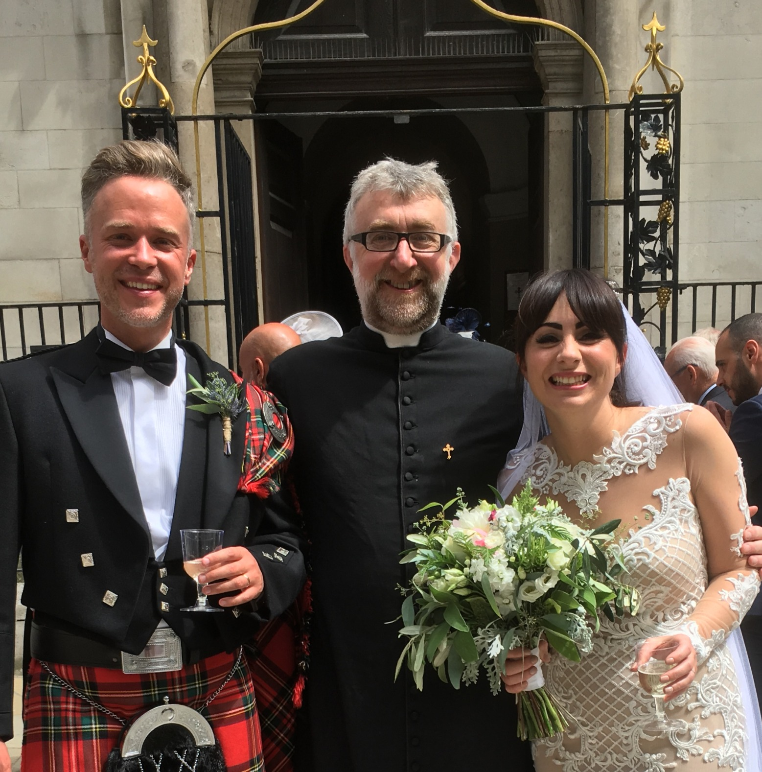 Fr Tim smiling with a couple just married outside St James Garlickhythe