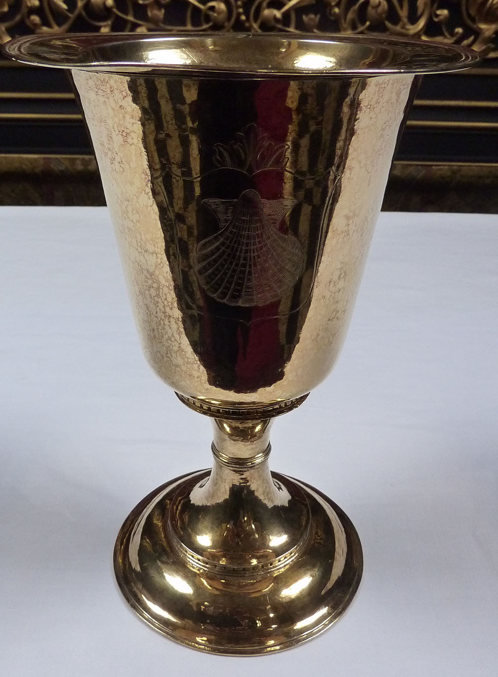 A gold chalice with a scallop carved into the front