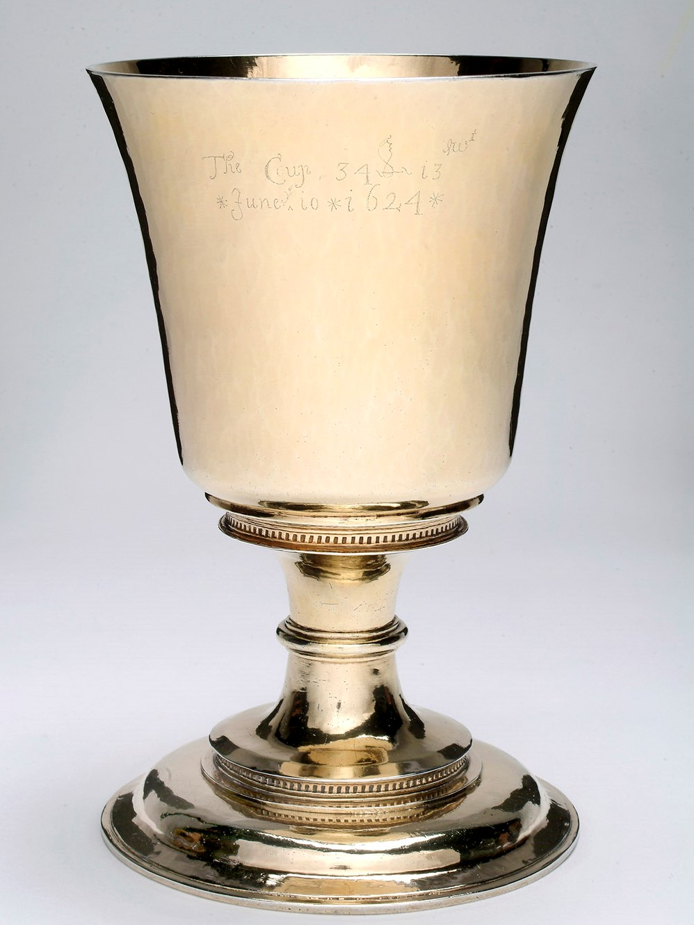 A gold chalice with writing lightly carved onto the front