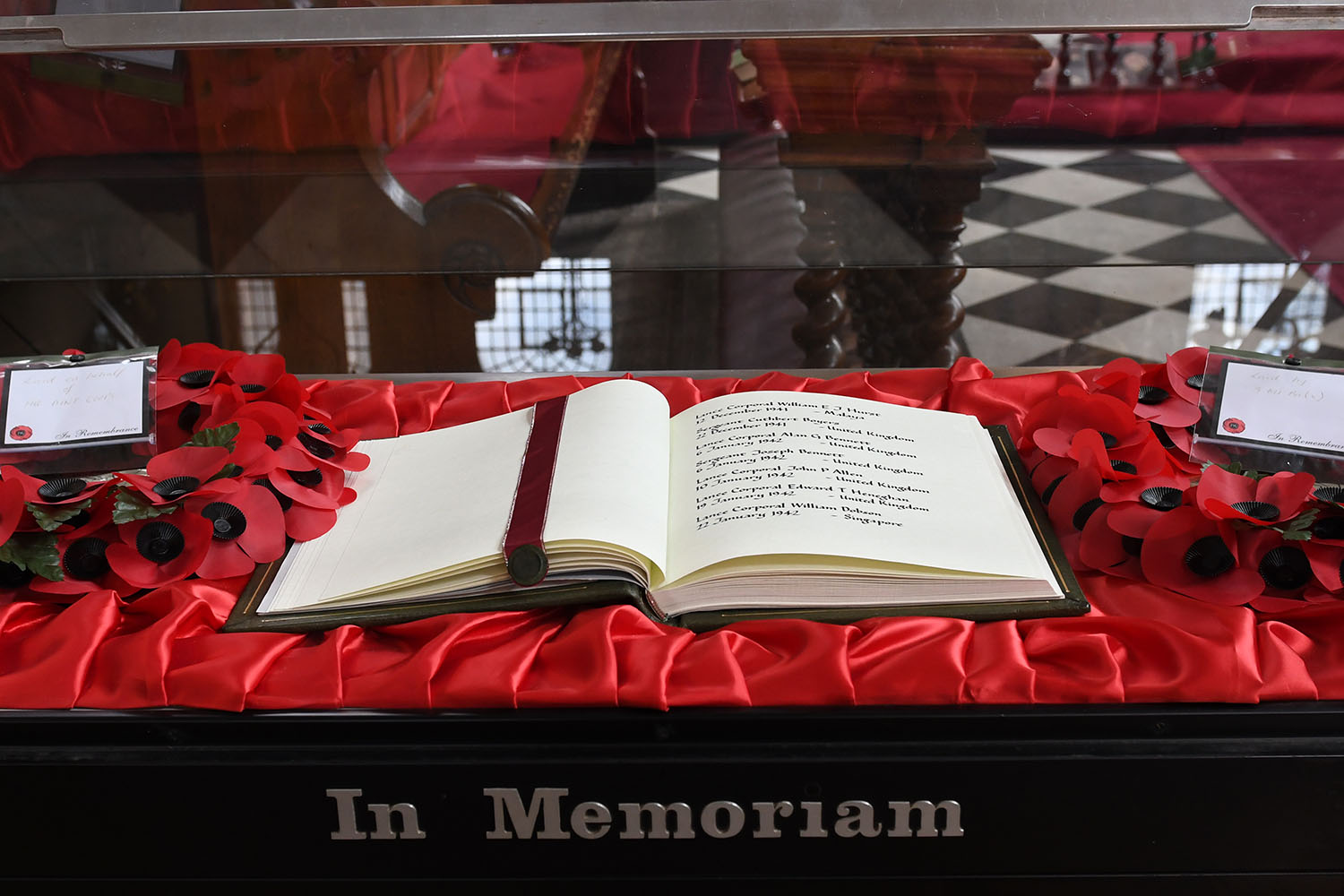 An open book of remembrance on a table with red silk and poppies, marked 'In Memoriam'.