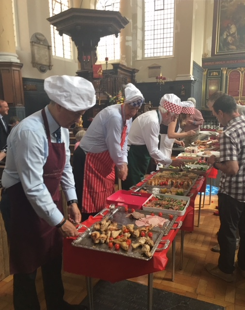 Chefs serve food on tables in St James Garlickhythe for the parish Patronal Festival