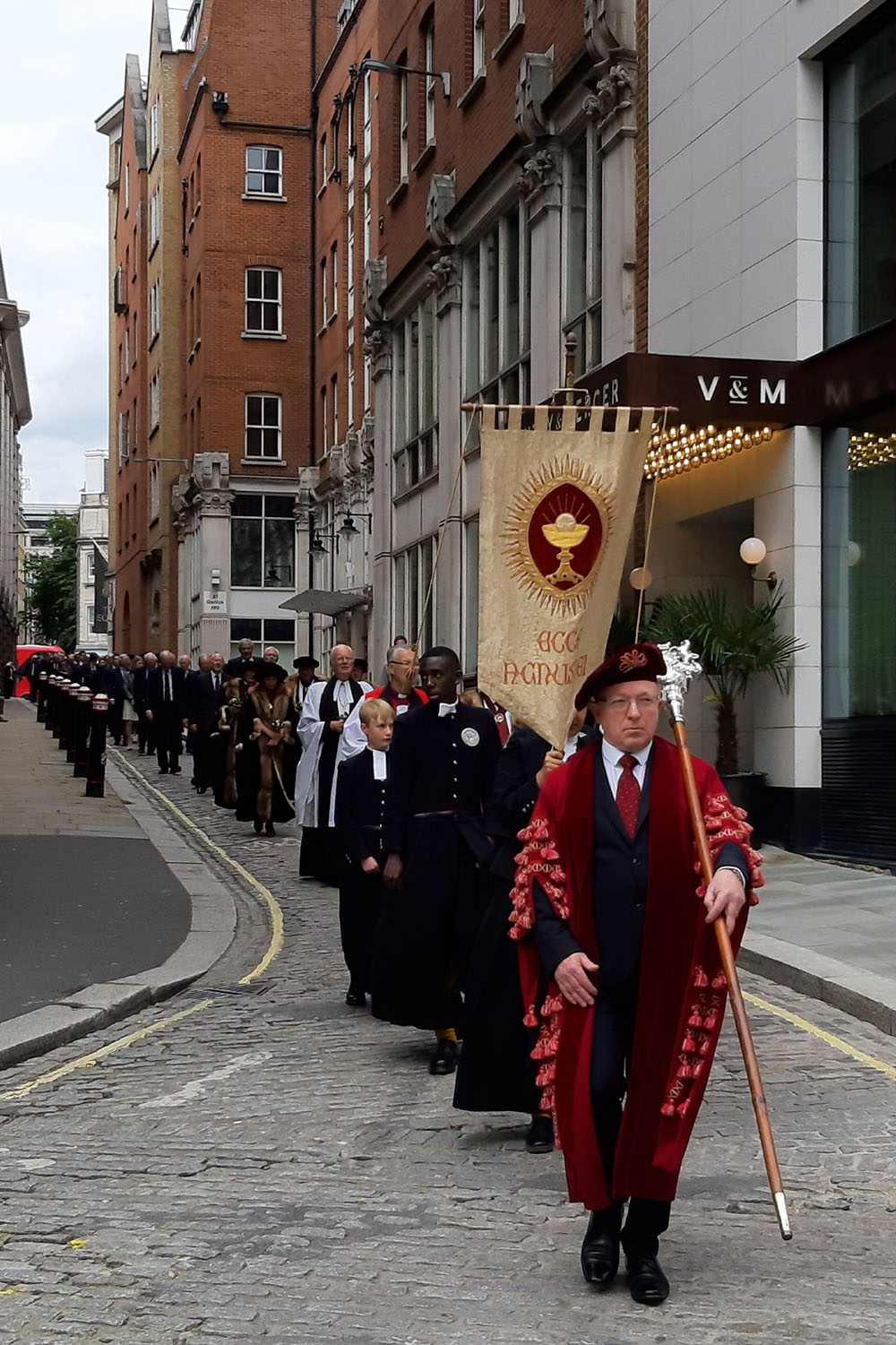 A line of people in traditional dress, The Worshipful Company of Skinners, process to St James along a London street holding a flag